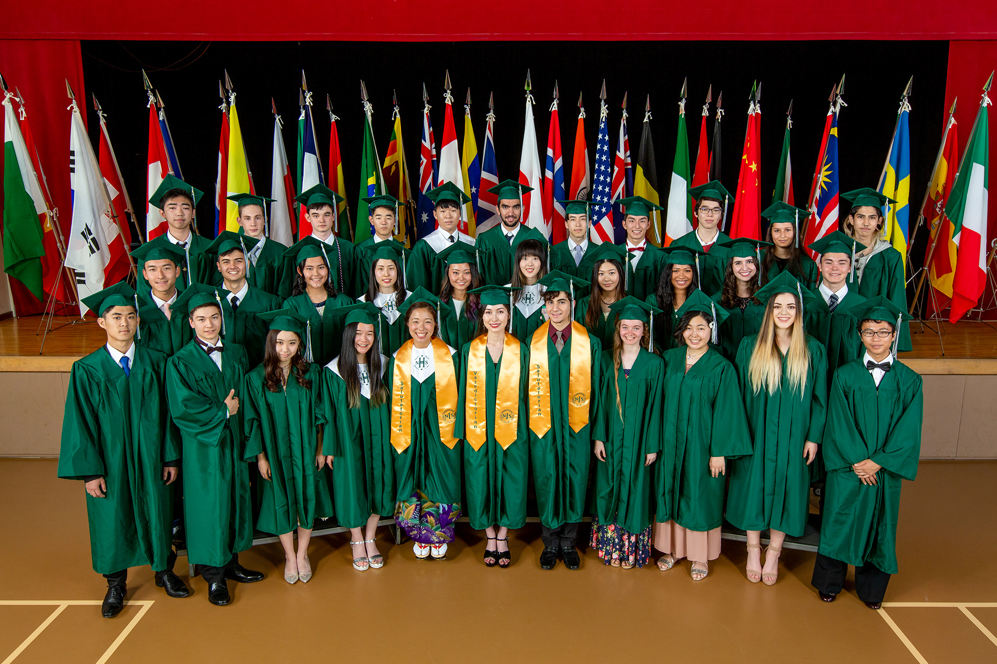 Boys and girls in green gowns smiling and posing for a photo